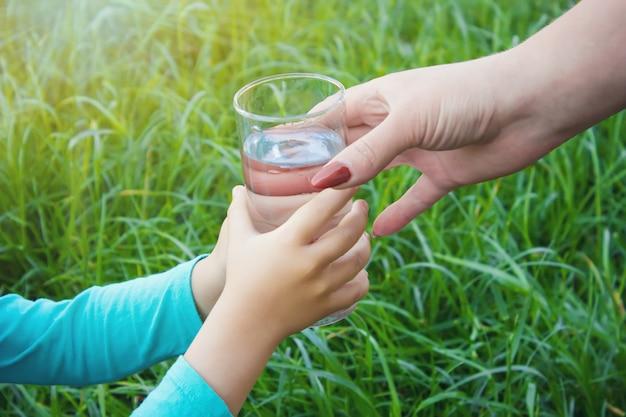 Das kind nimmt ein glas wasser. selektiver fokus