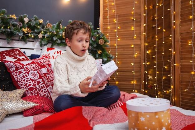 Das kind öffnet das geschenk. ein fröhlicher junge öffnete eine schachtel mit weihnachtsferien. frohe weihnachten und schöne feiertage!