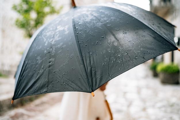 Das kind posiert mit einem regenschirm, ein kleines mädchen in einem kleid steht draußen unter einem schwarzen regenschirm