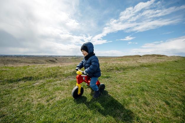 Das kind reist. junge auf einem dreirad im berg. familienreisen
