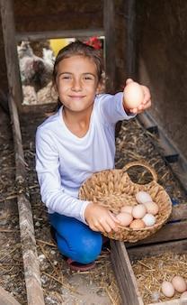 Das kind sammelt die eier im hühnerstall auf. selektiver fokus.