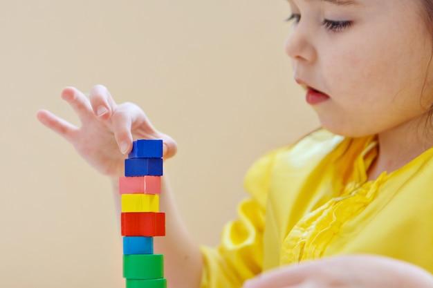 Das kind sammelt eine pyramide. details des spielzeugs in den händen. konzept der entwicklung von feinmotorik, lernspielen, kindheit, ivf, kindertag, kindergarten-kopierraum
