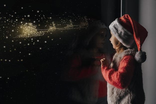 Das kind schaut zu weihnachten jesu christi aus dem fenster.