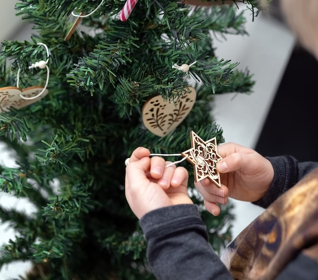 Das kind schmückt den weihnachtsbaum hände halten eine dekorative schneeflocke einen stern nahaufnahme