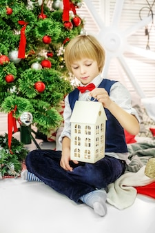 Das kind sitzt am weihnachtsbaum und spielt