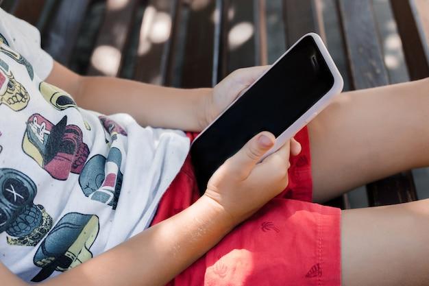 Das kind sitzt im park auf einer bank mit einem gerät. kinder benutzen geräte. ein junge spielt ein spiel auf einem handy.