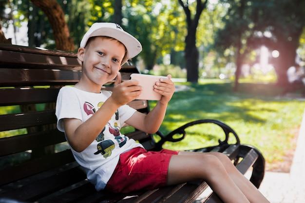 Das kind sitzt im park auf einer bank mit einem gerät. kinder benutzen geräte. porträt eines schönen jungen in der untergehenden sonne. ein junge spielt ein spiel auf einem handy.