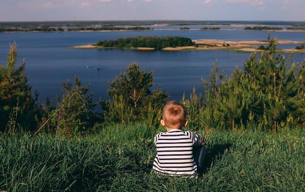 Das kind sitzt mit seinem rücken auf dem gras am ufer eines großen flusses