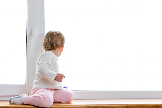 Das kind sitzt und schaut aus dem fenster