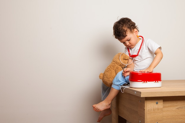 Das kind spielt im arzt mit einem teddybär und einem spielzeug-erste-hilfe-kasten
