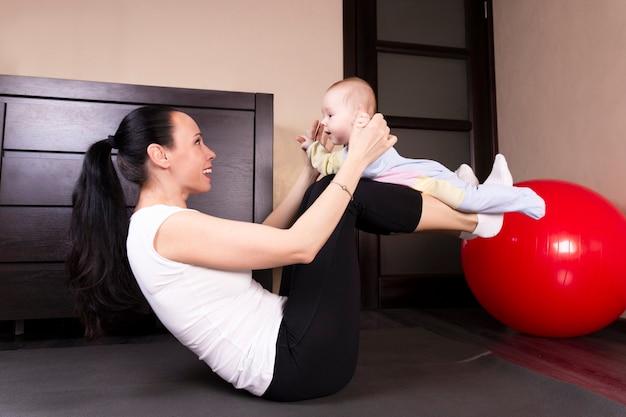 Das kind spielt, macht übungen, macht gymnastik mit seiner mutter zu hause.
