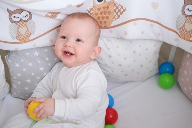 Das kind spielt mit bunten bällen in der krippe.
