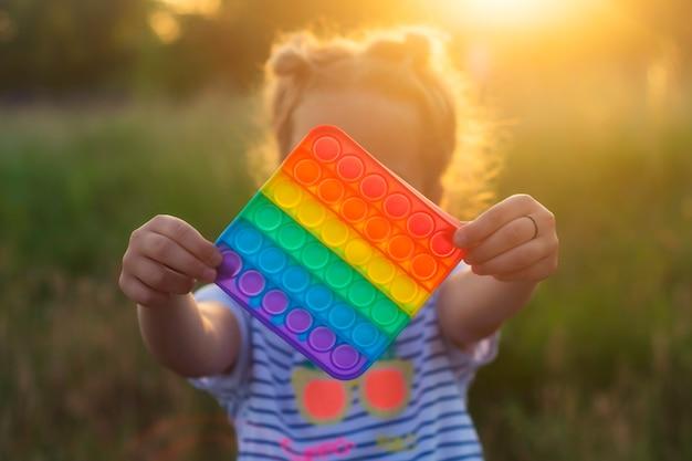 Das kind spielt mit einem bunten regenbogenspiel mohn. silikon zappeln nahaufnahme.