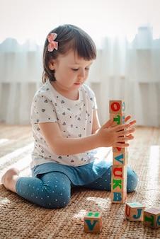 Das kind spielt mit holzklötzen mit buchstaben auf dem boden in dem raum, in dem ein kleines mädchen zu hause oder im kindergarten einen turm baut.