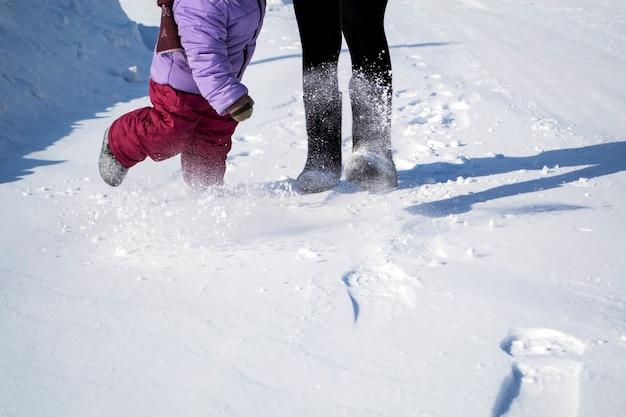Das kind und seine mutter gingen händchen haltend im winter spazieren