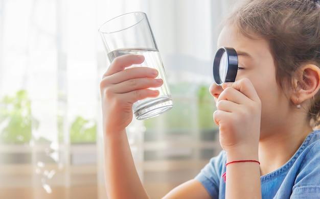 Das kind untersucht das wasser mit einer lupe in einem glas