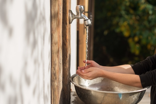 Das kind wäscht seine hände in einem metallwaschbecken im land hände des kindes hygienekonzept