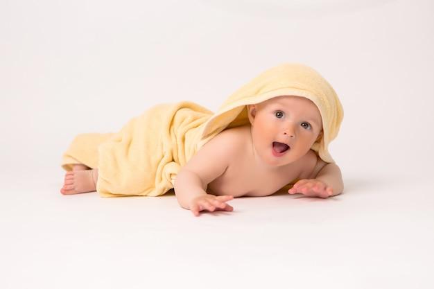 Das kind wird nach dem baden in ein gelbes weiches handtuch gewickelt.