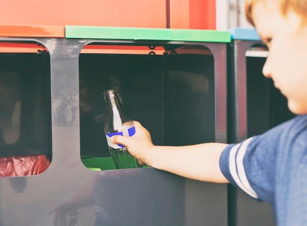 Das kind wirft die glasflasche in einen von vier mülleimern zum sortieren von müll