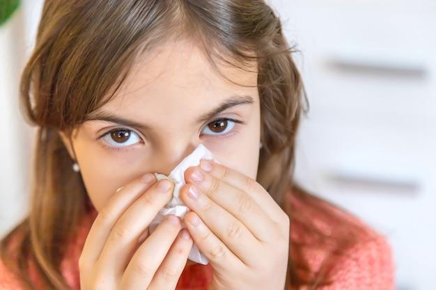 Das kind wischt sich mit einer serviette eine laufende nase ab. selektiver fokus. menschen.