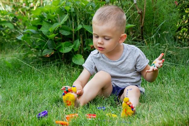Das kind zeichnet ein muster auf das bein. eine lustige zeichnung mit hellen farben auf dem körper. selektiver fokus
