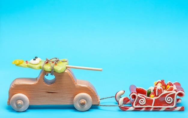 Das kinderauto aus holz trägt eine karamell-fichte und zieht einen schlitten mit geschenken