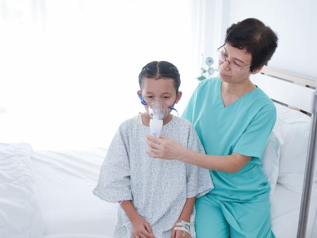 Das kleine asiatische mädchen, das auf bett im krankenhauszimmer und in der älteren krankenschwester legt, wart mach's gut daneben.