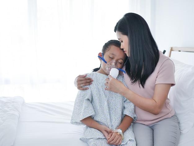 Das kleine asiatische mädchen, das auf bett im krankenhauszimmer und in ihrer mutter legt, war kümmern sich neben.