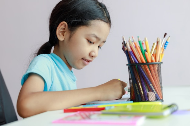 Das kleine asiatische mädchen, das hausarbeit tuend setzt, benutzen farbbleistift, um auf papier zu zeichnen