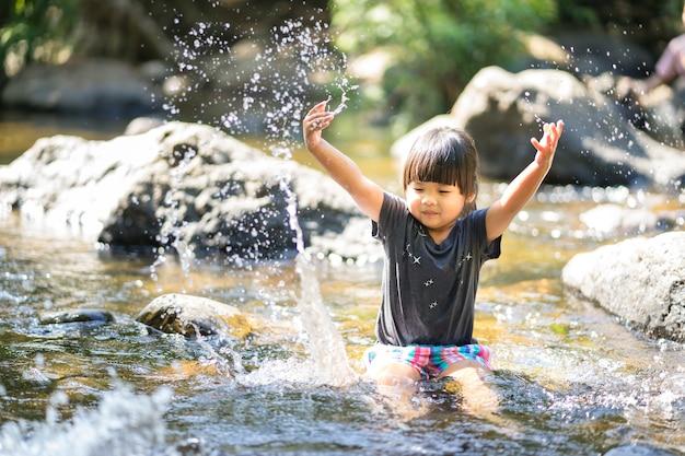 Das kleine asiatische mädchen, das im wasserfall spielt, strömen mit wasserspritzen
