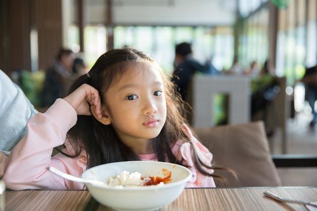 Das kleine asiatische mädchengefühl langte das lebensmittel mit der reis- und tomatensauce