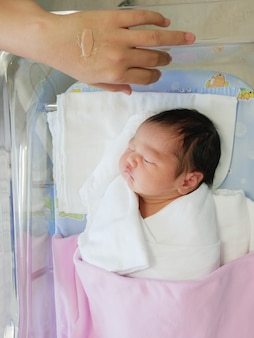 Das kleine asiatische neugeborene, das auf einem bett im krankenhaus schläft