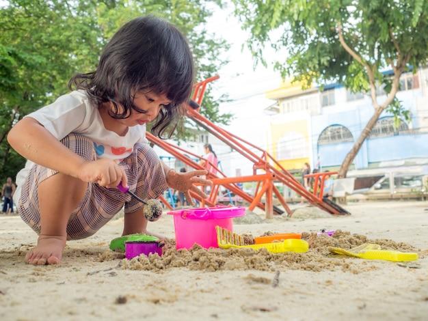 Das kleine asien-mädchen, das im sandkasten sitzt und whitspielzeug-schaufeleimer und sie spielt, schaufelte