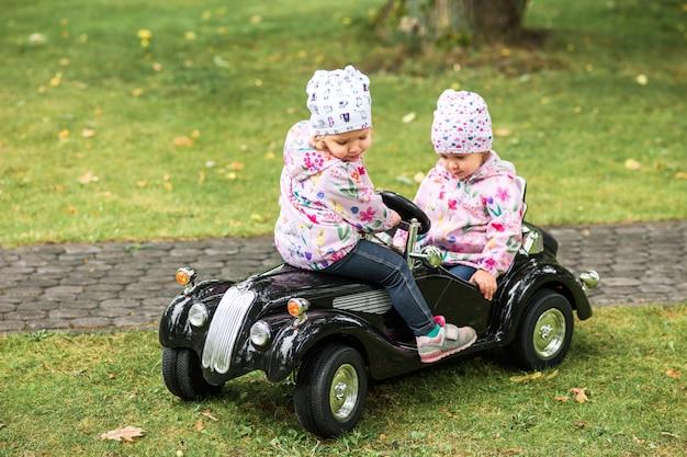 Das kleine baby, das am auto gegen grünes gras spielt