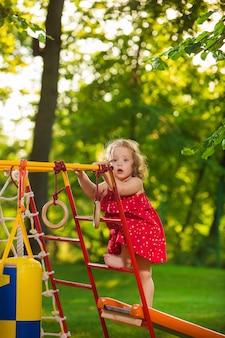 Das kleine baby, das am spielplatz im freien gegen grünes gras spielt