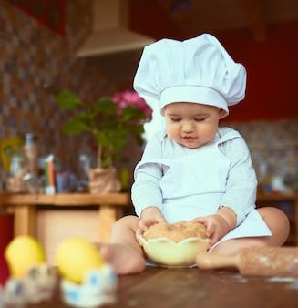 Das kleine baby, das auf dem tisch sitzt und mit teig spielt