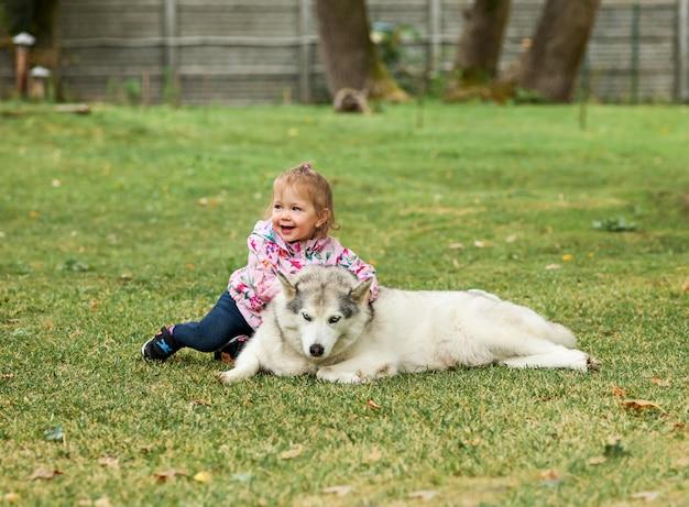 Das kleine baby, das mit hund gegen grünes gras im park spielt