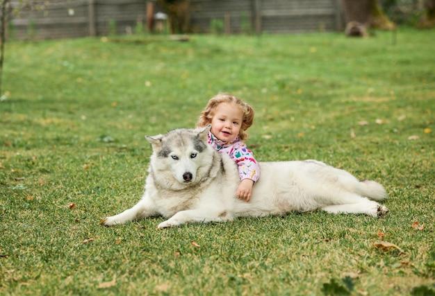 Das kleine baby, das mit hund gegen grünes gras spielt
