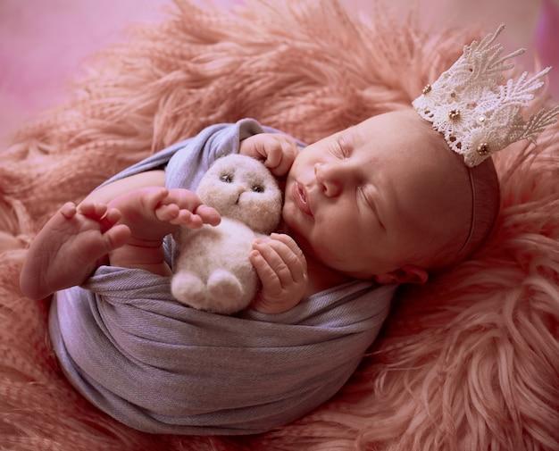 Das kleine baby mit krone liegt im korb