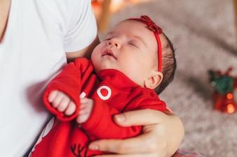 Das kleine Baby schläft auf den Händen der Mütter