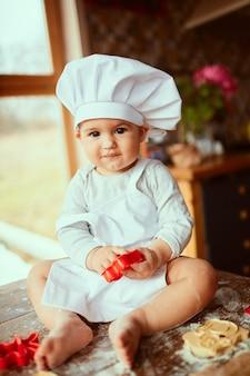 Das kleine baby sitzt auf dem tisch in der nähe von teig
