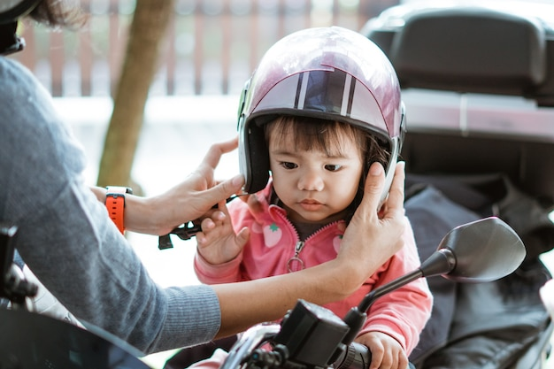 Das kleine baby trägt einen motorradhelm, wenn es von seiner mutter am motorrad befestigt wird