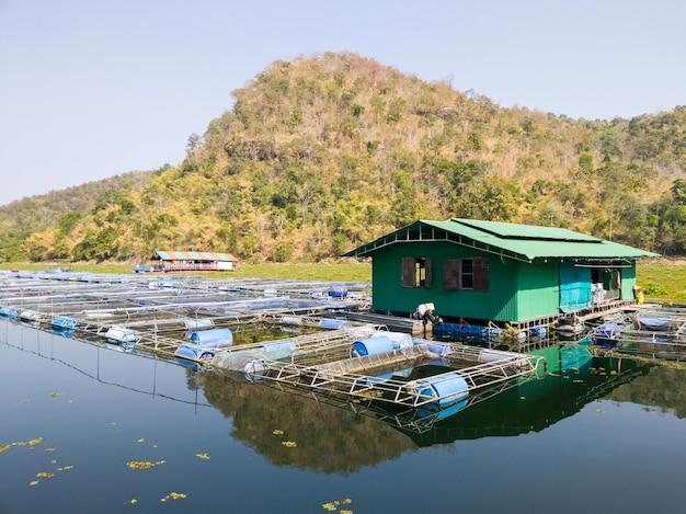 Das kleine gewächshaus des fischers schwimmt in der nähe des fischzuchtkäfigs im großen stausee des damms