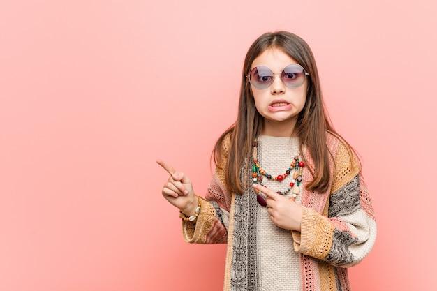 Das kleine hippie-mädchen zeigte schockiert mit den zeigefingern auf eine leere stelle.