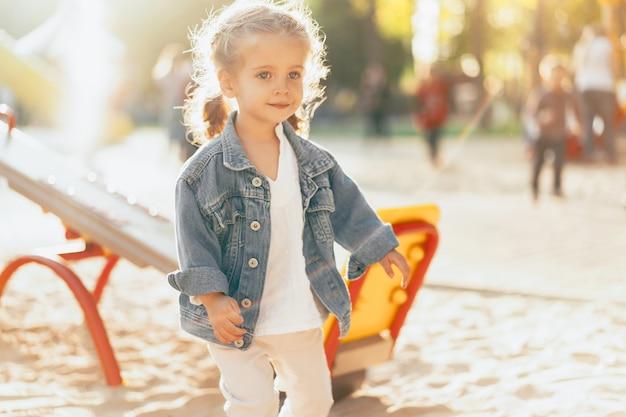 Das kleine kaukasische mädchen, das in einer denimjacke gekleidet wird, wird auf dem spielplatz an einem hellen sonnigen tag gespielt