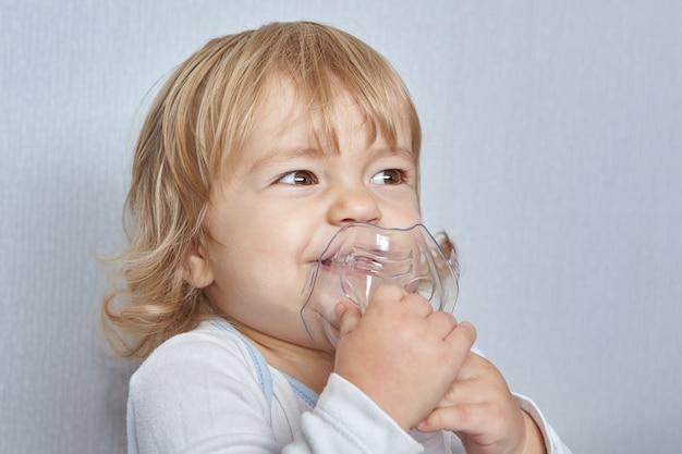 Das kleine kaukasische mädchen, ungefähr 1,5 jahre alt, atmet mit einer speziellen maske, um den asthmaanfall zu stoppen.