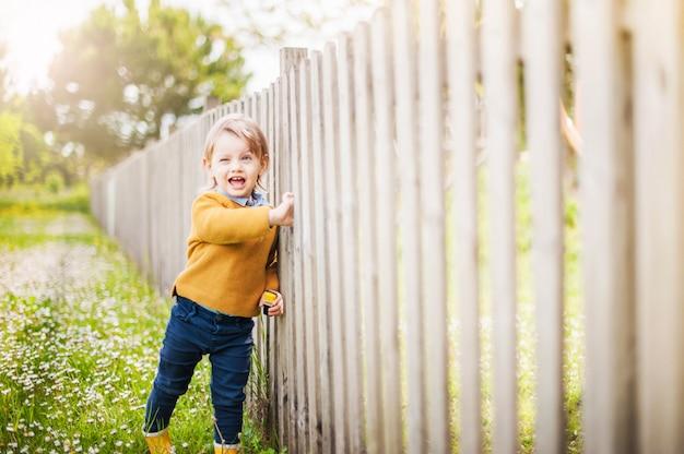Das kleine kind, das die gelben regenstiefel, lächelnd mit einem auge trägt, schloss