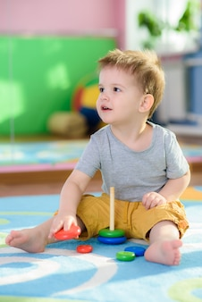 Das kleine kind sammelt eine pirimda, die auf einem fußboden sitzt