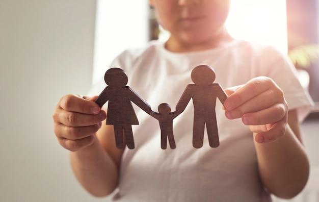 Das kleine kind schaut auf die holzfiguren von mama, papa und kind in seinen händen. konzept des kindes, das von der familie träumt