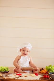 Das kleine kind sitzt auf dem tisch in der nähe von teig und gemüse
